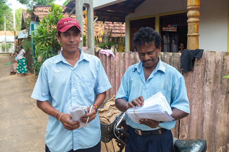 17 years: WELIGAMA, SRI LANKA - MARCH 8, 2014: Two postmen delivering post to local people. Sri Lanka Posts has been in existence for more than 209 years and employs more than 17,000 employees.