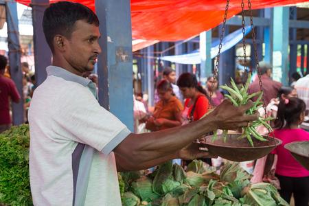 sunday market: HIKKADUWA, SRI LANKA - 09 de marzo 2014: frijoles con un peso de vendedores ambulantes Local. El mercado de los domingos es una gran manera de ver la vida local de Hikkaduwa cobran vida junto con productos frescos y delicadeza local