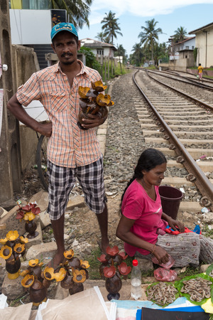 HIKKADUWA, SRI LANKA - MARCH 9, 2014: Local street vendor couple selling coconut decorations by the railroad. The Sunday market is a fantastic way to see Hikkaduwas local life come alive.
