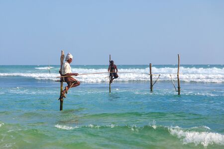 earn more: UNAWATUNA, SRI LANKA - MARCH 9, 2014: Stilt Fishermen at Unawatuna. Many of these fishermen earn more money posing for tourists than fishing fish.