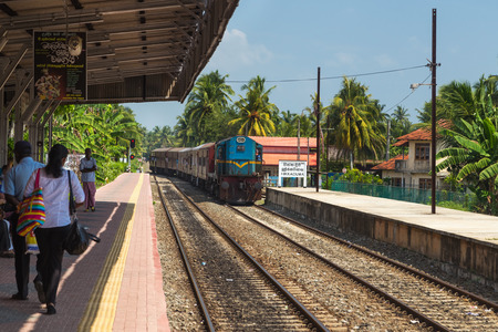 poorly: HIKKADUWA, SRI LANKA - MARCH 12, 2014: Train approaching Hikkaduwa train station. Trains are very cheap and poorly maintained but its the best option to witness a bit of everyday local life.