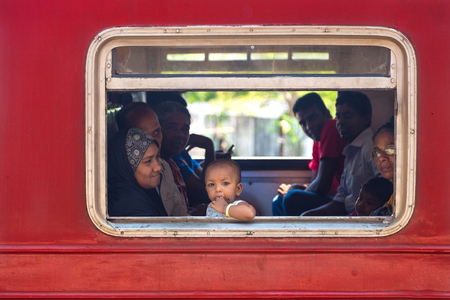 HIKKADUWA, SRI LANKA - MARCH 12, 2014: Local people in train looking through window. Trains are very cheap and poorly maintained but its the best option to witness a bit of everyday local life.