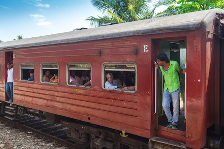poorly: HIKKADUWA, SRI LANKA - MARCH 12, 2014: Local commuters in old train. Trains are very cheap and poorly maintained but its the best option to witness a bit of everyday local life. Editorial