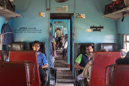 poorly: HIKKADUWA, SRI LANKA - MARCH 12, 2014: Commuters sitting in train to Colombo. Trains are very cheap and poorly maintained but its the best option to witness a bit of everyday local life.