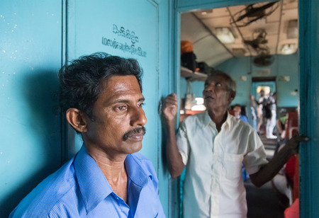 poorly: HIKKADUWA, SRI LANKA - MARCH 12, 2014: Two local men standing in train. Trains are very cheap and poorly maintained but its the best option to witness a bit of everyday local life. Editorial