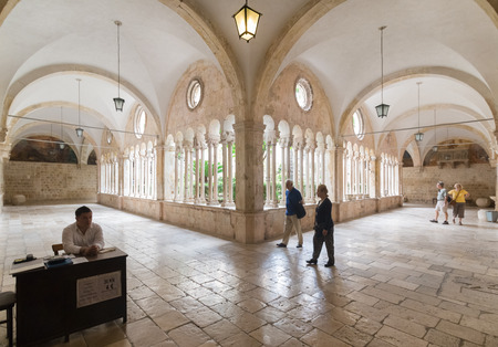 transitional: DUBROVNIK, CROATIA - MAY 26, 2014: Tourists in hallway around famous courtyard in Monastery of the Friars minor. It is the most important work from transitional period from Romanesque to Gothic style Editorial