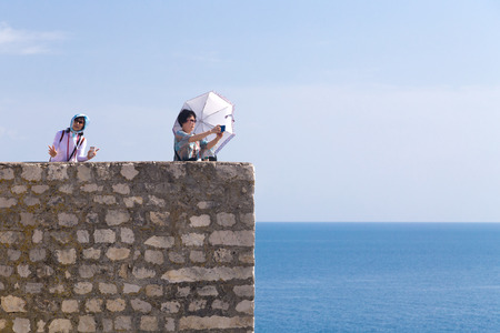 feature wall: DUBROVNIK, CROATIA - MAY 26, 2014: Asian tourists at Old city walls with Adriatic sea in background. Old wall is one of Dubrovniks most famous feature. It is almost 2 km long. Editorial