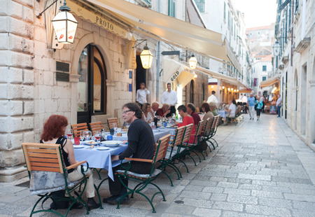 DUBROVNIK, CROATIA - MAY 28, 2014: Guests sitting at Proto restaurant terrace, one of Dubrovniks best known places for fish specialities. Editorial