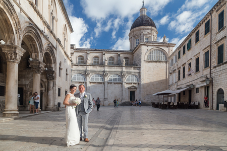 DUBROVNIK, CROATIA - MAY 28, 2014: Groom and bride posing in front of the Rector Palace. Streets of Dubrovniks Old town are very popular for wedding photo sessions.