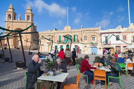 our people: MARSAXLOKK, MALTA - JANUARY 11, 2015: People eating at restaurant terrace in front of the Parish Church of Our Lady of Pompei.