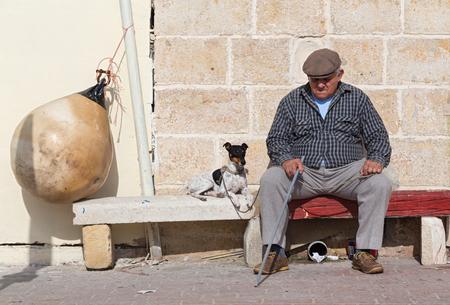 MARSAXLOKK, MALTA - JANUARY 11, 2015: Elderly man with dog sitting on the street bench.