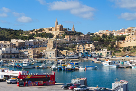 the church of our lady: MGARR, MALTA - JANUARY 13, 2015: Mgarr harbour with view of church Our Lady of Lourdes on top of the hill, Gozo island.