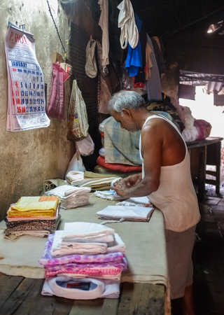 ironed: MUMBAI, INDIA - 08 JANUARY 2015: Indian worker tagging clean ironed cloths in Dhobi ghat. Editorial