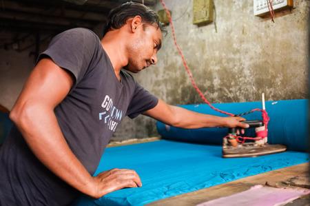 dhobi ghat: MUMBAI, INDIA - 08 JANUARY 2015: Man ironing with an electric iron indoors in Dhobi ghat.