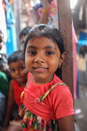 dhobi ghat: MUMBAI, INDIA - 08 JANUARY 2015: Young girl living in Dhobi ghat looking at camera