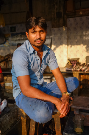dhobi ghat: MUMBAI, INDIA - 08 JANUARY 2015: Worker on a fishmarket next to Dhobi ghat posing while waiting for customers.
