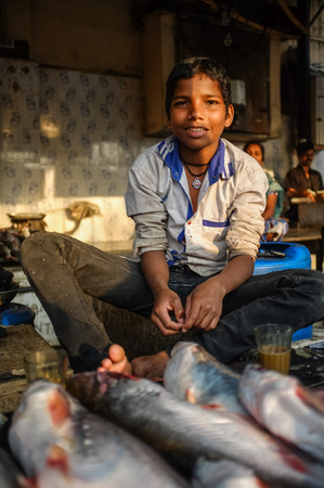 MUMBAI, INDIA - 08 JANUARY 2015: Young worker on a fishmarket next to Dhobi ghat posing while waiting for customers. Editorial