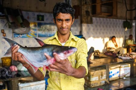 MUMBAI, INDIA - 08 JANUARY 2015: Worker on a fishmarket next to Dhobi ghat showing a fish while waiting for customers. Editorial