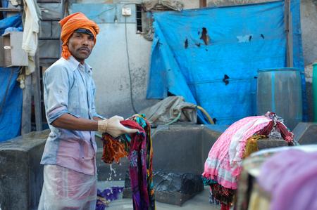 MUMBAI, INDIA - 10 JANUARY 2015: Indian worker washing a sari in Dhobi ghat. Editorial