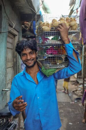 MUMBAI, INDIA - 10 JANUARY 2015: Indian worker carrying cage full of young poultry.
