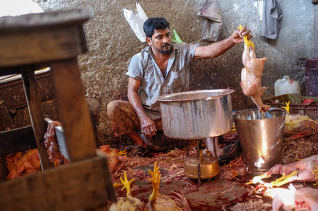 skinning: MUMBAI, INDIA - 11 JANUARY 2015: Worker cleaning dead chicken on Andheri market. Editorial