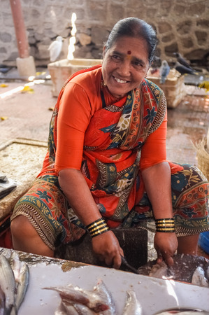 MUMBAI, INDIA - 11 JANUARY 2015: Woman cleaning fish on a fishmarket. Editorial