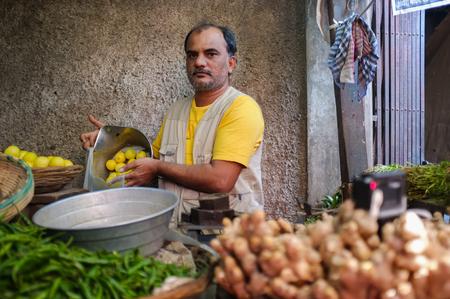 vendor: MUMBAI, INDIA - 11 JANUARY 2015: Vendor in Andheri fruit market putting lemons in bag.