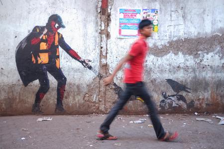 spiderman: MUMBAI, INDIA - 12 JANUARY 2015: Graffiti art of Spiderman in Dharavi slum while man passes