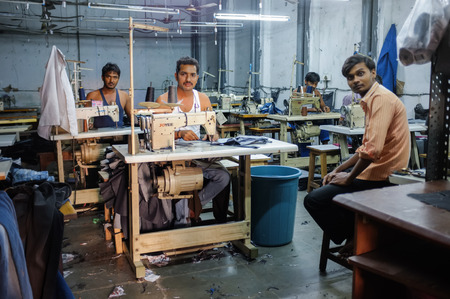 MUMBAI, INDIA - 12 JANUARY 2015: Indian workers sowing in a clothing factory in Dharavi slum