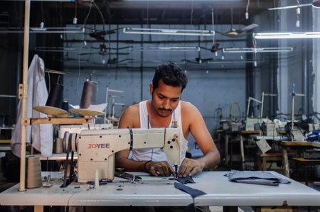 textile industry: MUMBAI, INDIA - 12 JANUARY 2015: Indian worker sews in clothing factory in Dharavi slum. Post-processed with grain, texture and colour effect.