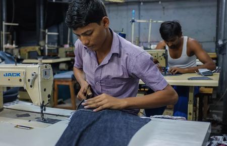 maquinas de coser: MUMBAI, INDIA - 12 de enero de 2015: los trabajadores indios de coser en una fábrica de ropa en Dharavi tugurios