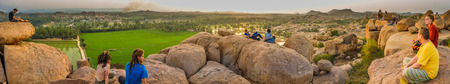 paddies: HAMPI, INDIA - 29 JANUARY 2015: Hilltop view of Hampis boulder strewn landscape and rice paddies with tourists Editorial