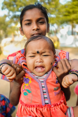 bindi: HAMPI, INDIA - 31 JANUARY 2015: Indian baby with bindi crying while being held by family member