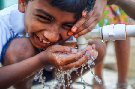 HAMPI, INDIA - 31 de enero de 2015: niño indio siendo molestado mientras bebe agua de una fauset Foto de archivo - 39215681