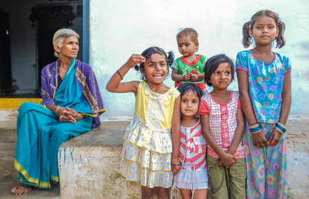 indian village: HAMPI, INDIA - 31 JANUARY 2015: Indian family members standing infront of house. Grandmother overlooking her five grandaughters