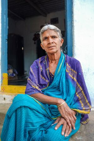 nosering: HAMPI, INDIA - 31 JANUARY 2015: Elderly Indian woman sitting in a sari infront of her home