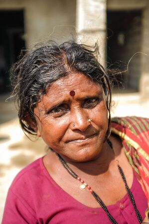 bindi: HAMPI, INDIA - 01 FEBRUARY 2015: Indian middle-aged woman with bindi on street infront of home