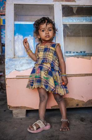 niños pobres: Kamalapuram, INDIA - 02 FABRUARY 2015: niño indio de pie dentro de una tienda en un mercado cerca de Hampi