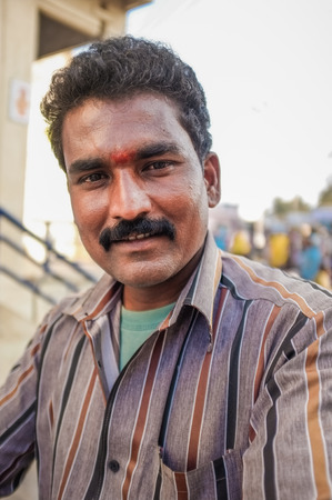 strip shirt: KAMALAPURAM, INDIA - 02 FABRUARY 2015: Indian man on a marketplace close to Hampi Editorial