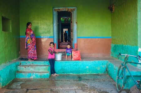 thier: KAMALAPURAM, INDIA - 02 FABRUARY 2015: Indian family outside thier home in a town close to Hampi Editorial