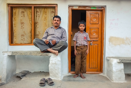 ouside: KAMALAPURAM, INDIA - 02 FABRUARY 2015: Father and son ouside their home in a town close to Hampi