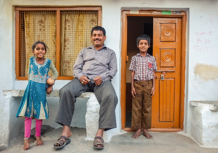 KAMALAPURAM, INDIA - 02 FABRUARY 2015: Father and his two children infront of their home in a town close to Hampi