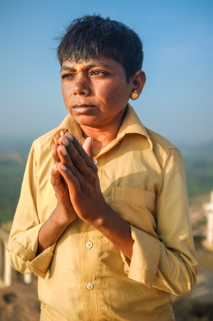 spiritualism: KAMALAPURAM, INDIA - 03 FEBRUARY: Indian pilgrim with hands in praying position on hilltop