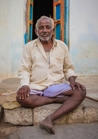 men shirt: KAMALAPURAM, INDIA - 02 FABRUARY 2015: Indian elderly man sitting infront of his home Editorial