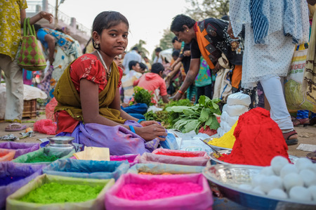 KAMALAPURAM, INDIA - 02 FABRUARY 2015: Young Indian girl selling colored powder on a market close to Hampi