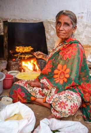 indian fair: KAMALAPURAM, INDIA - 02 FABRUARY 2015: Elderly Indian woman in traditional clothes frying vegatables on a market close to Hampi