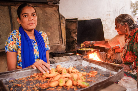nosering: KAMALAPURAM, INDIA - 02 FABRUARY 2015: Young Indian woman selling fried chilli while her mother makes them in the background