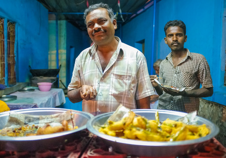 indian village: KAMALAPURAM, INDIA - 02 FABRUARY 2015: Two Indian family members inside their restaurant waiting for customers Editorial