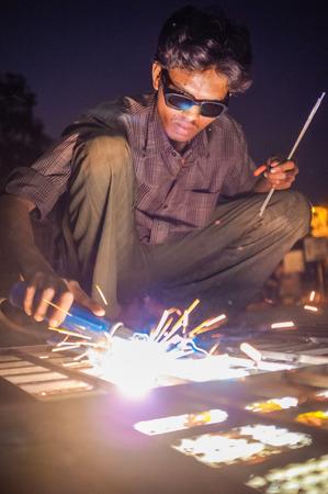 asian produce: KAMALAPURAM, INDIA - 02 FABRUARY 2015: Indian worker welding heavy metal parts on street in dusk