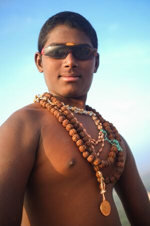 spiritualism: KAMALAPURAM, INDIA - 03 FEBRUARY: Young Indian pilgrim with religious necklaces and sunglasses on hilltop Editorial